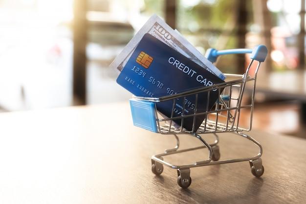 Carrinho de compras com cartões de crédito e dinheiro na mesa