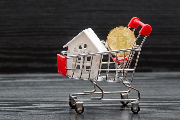Carrinho de compras com casa branca e moeda bitcoin