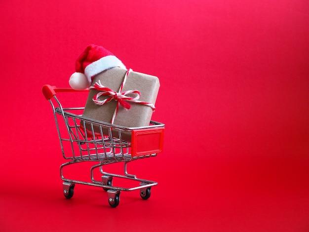 Carrinho de compras com chapéu de papai noel vermelho e presente de natal, sobre fundo vermelho.