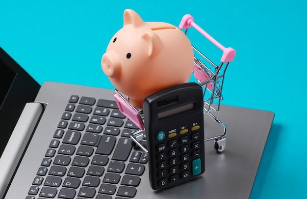Carrinho de compras com cofrinho e calculadora no close up do teclado do laptop