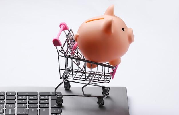 Carrinho de compras com cofrinho no teclado do laptop