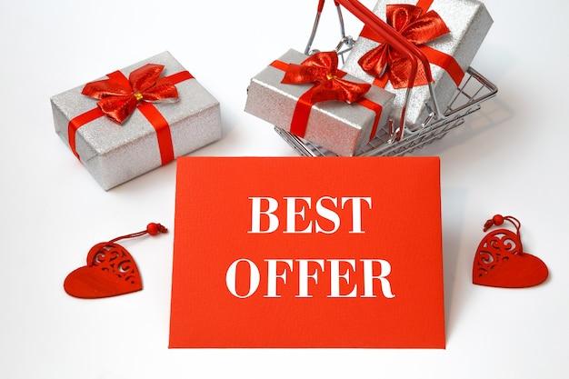 Carrinho de compras com compras na época festiva e o texto melhor oferta no cartão vermelho