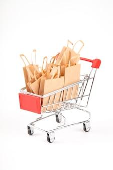 Carrinho de compras com compras. pacotes no fundo branco isolado. venda. uso de materiais ecológicos. desperdício zero