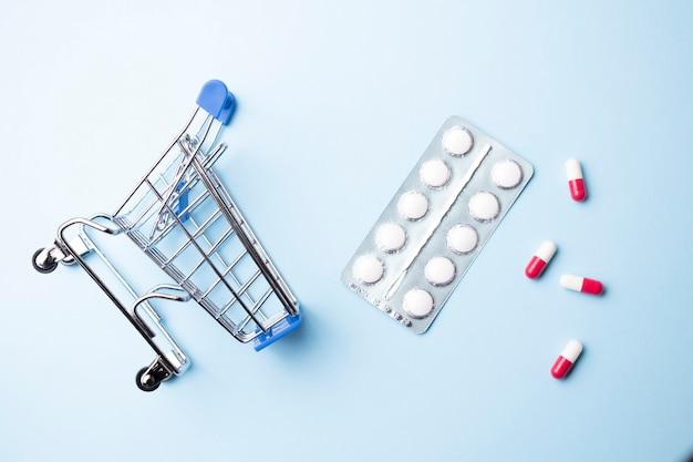 Carrinho de compras com comprimidos de remédios variados sobre fundo azul claro.