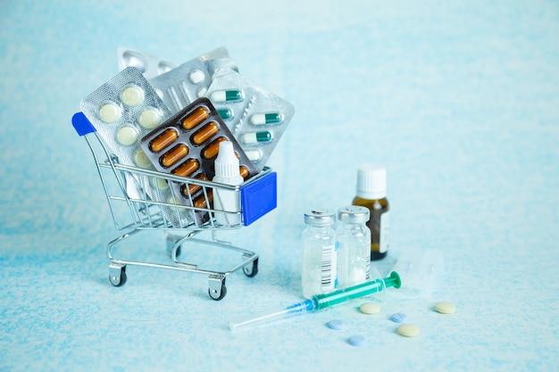 Carrinho de compras com comprimidos em uma superfície azul