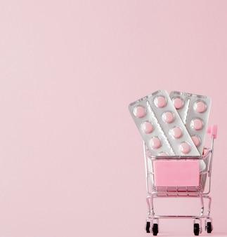 Carrinho de compras com comprimidos médicos na parede rosa com espaço de cópia