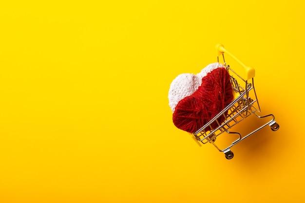 Carrinho de compras com corações feitos à mão voa sobre um fundo amarelo brilhante.