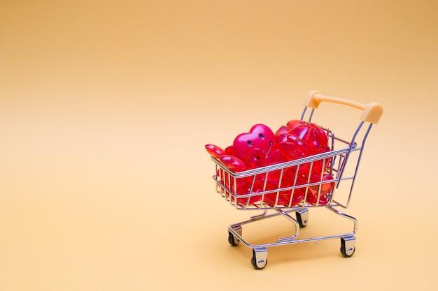 Carrinho de compras com corações vermelhos em um fundo amarelo