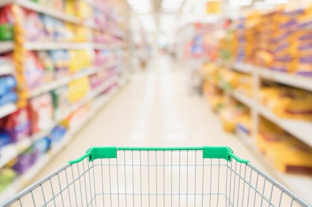 Carrinho de compras com desfoque abstrato de supermercado loja de descontos e prateleiras de produtos de ração para animais de estimação com fundo desfocado
