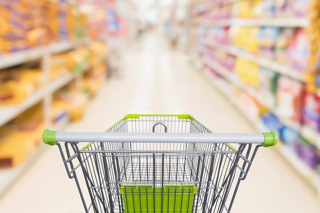 Carrinho de compras com desfoque abstrato no corredor da loja de descontos de supermercado e prateleiras de produtos de ração