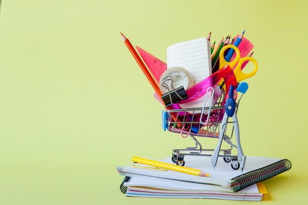 Carrinho de compras com diferentes artigos de papelaria no fundo amarelo