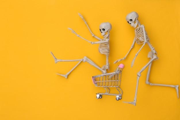 Carrinho de compras com esqueletos engraçados sobre fundo amarelo. tema de halloween. vista do topo