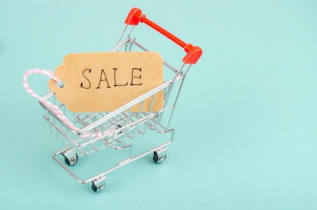 Carrinho de compras com etiqueta de venda em superfície brilhante