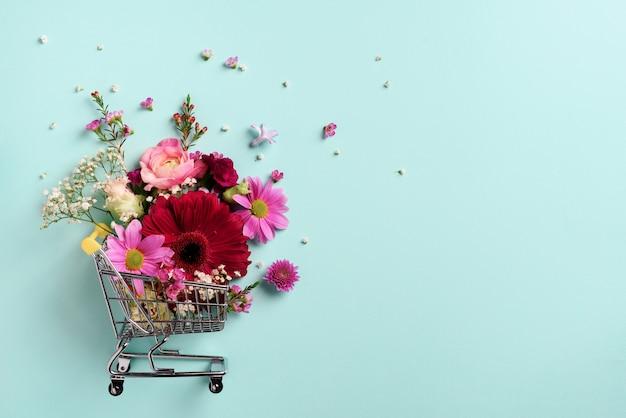 Carrinho de compras com flores em fundo azul pastel pastel.