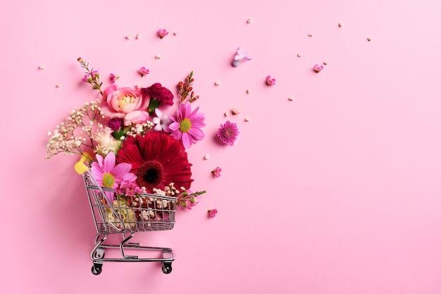 Carrinho de compras com flores sobre fundo rosa pastel ondulado.