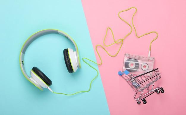 Carrinho de compras com fones de ouvido estéreo e fita cassete na superfície rosa azul