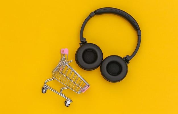 Carrinho de compras com fones de ouvido estéreo sem fio em um fundo amarelo. vista do topo