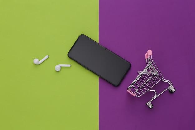 Carrinho de compras com fones de ouvido sem fio e smartphone em um fundo verde-púrpura.