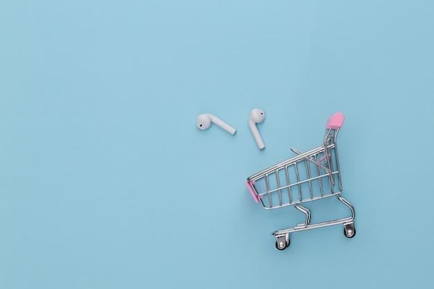 Carrinho de compras com fones de ouvido sem fio sobre fundo azul.