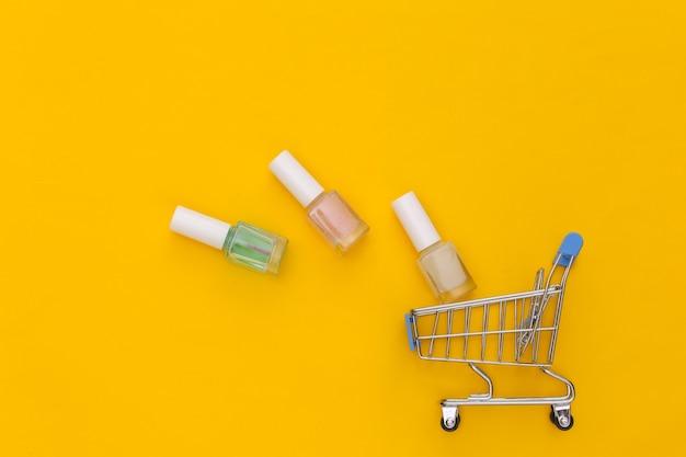 Carrinho de compras com frasco de esmalte em fundo amarelo. mercado de beleza. vista do topo