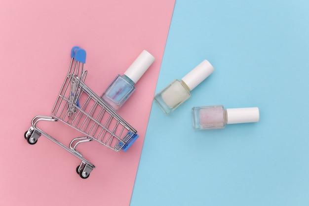 Carrinho de compras com frasco de esmalte em fundo rosa azul. mercado de beleza. vista do topo