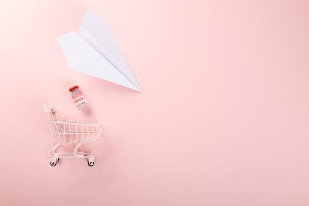 Carrinho de compras com frascos de vacinas para vacinação contra coronavírus e avião de papel