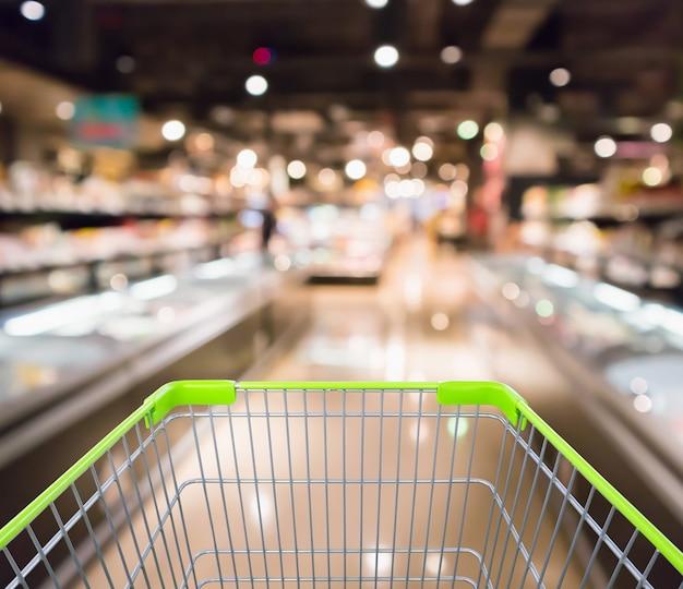 Carrinho de compras com geladeira de supermercado supermercado abstrato desfocado desfocado