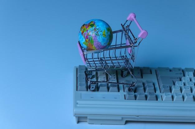 Carrinho de compras com globo no antigo teclado do pc. néon azul, luz holográfica. retro compras online