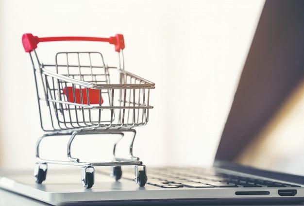 Carrinho de compras com laptop na mesa