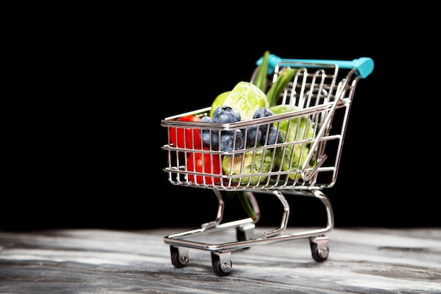 Carrinho de compras com legumes em fundo preto