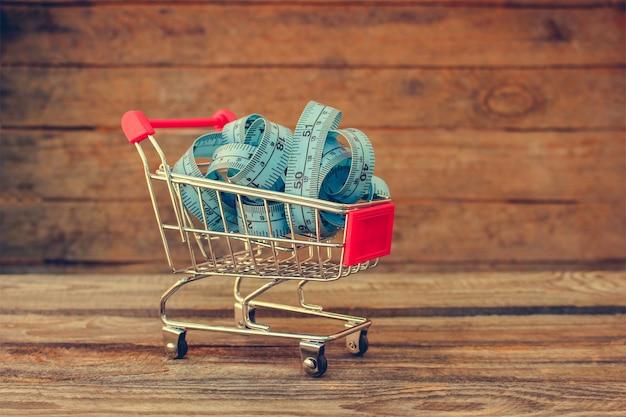 Carrinho de compras com linha de fita na madeira velha