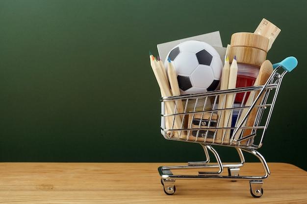 Carrinho de compras com material escolar sobre o quadro-negro verde