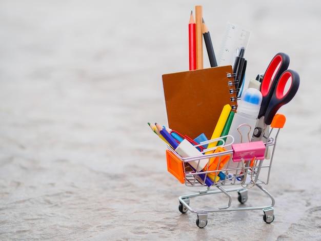 Carrinho de compras com material escolar. volta ao conceito de escola.
