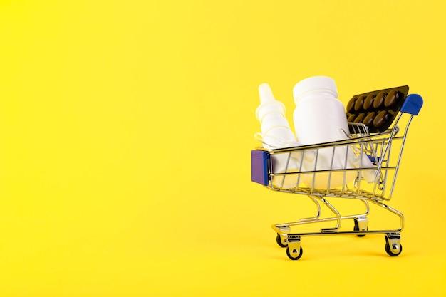 Carrinho de compras com medicamentos em fundo amarelo.