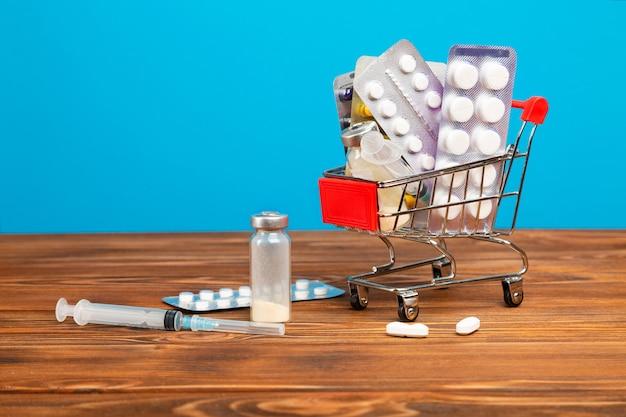 Carrinho de compras com medicamentos em uma mesa de madeira.