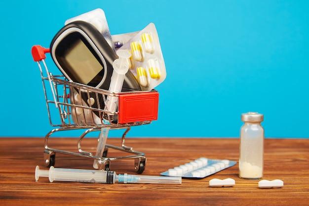 Carrinho de compras com medicamentos para diabetes mellitus em uma mesa de madeira.