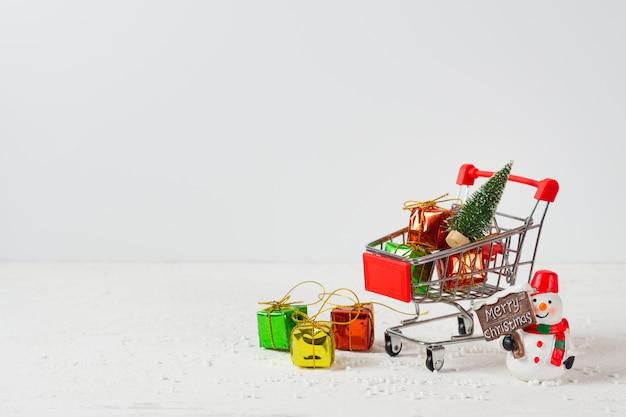 Carrinho de compras com mini árvore de natal, caixas de presente e boneco de neve