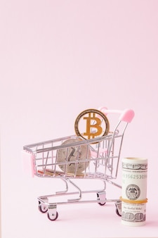 Carrinho de compras com moeda bitcoin e dólares em fundo rosa com espaço de cópia