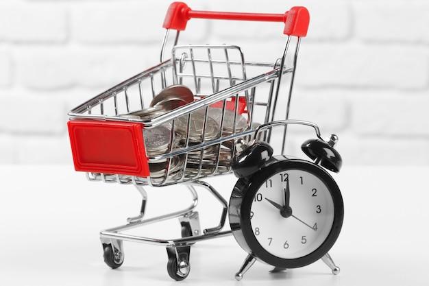 Carrinho de compras com moedas e relógio