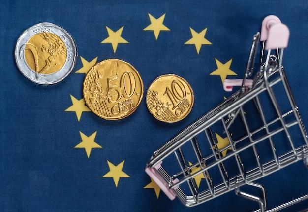 Carrinho de compras com moedas na bandeira da união europeia