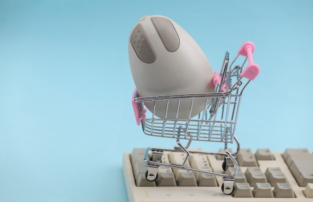 Carrinho de compras com mouse de pc retrô no antigo teclado de pc. fundo azul. atributos retro anos 80