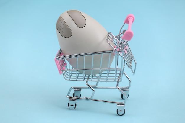 Carrinho de compras com mouse de pc retrô sobre fundo azul. atributos retro anos 80