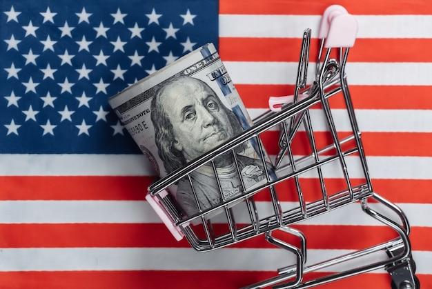 Carrinho de compras com notas de cem dólares na bandeira dos eua
