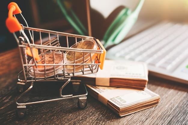 Carrinho de compras com notas de dólar na mesa com espaço de cópia - conceito de comércio eletrônico on-line de compras