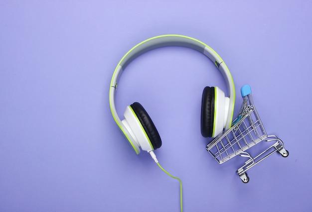 Carrinho de compras com novos fones de ouvido estéreo na superfície roxa