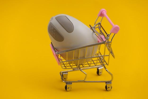 Carrinho de compras com o mouse de pc retrô em fundo amarelo. atributos retro anos 80