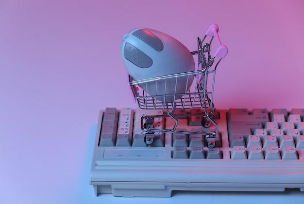 Carrinho de compras com o mouse do pc no teclado antigo. néon gradiente rosa azul, luz holográfica. atributos anos 80, onda retro