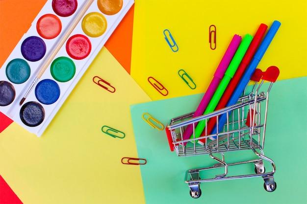 Carrinho de compras com objetos de papelaria. material escolar e escolar. de volta à escola.