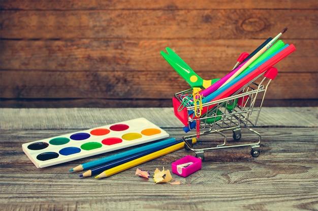 Carrinho de compras com objetos de papelaria. material escolar e escolar.