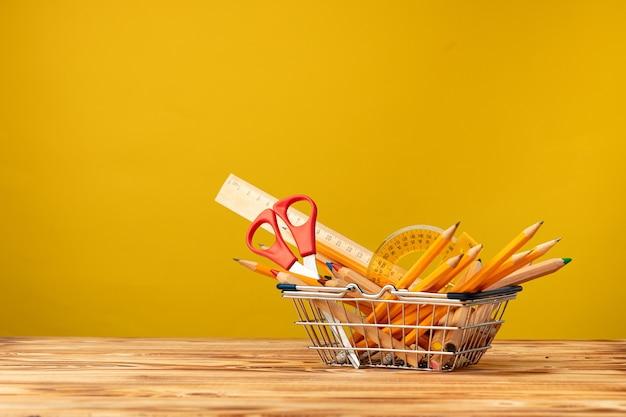 Carrinho de compras com papelaria escolar em amarelo